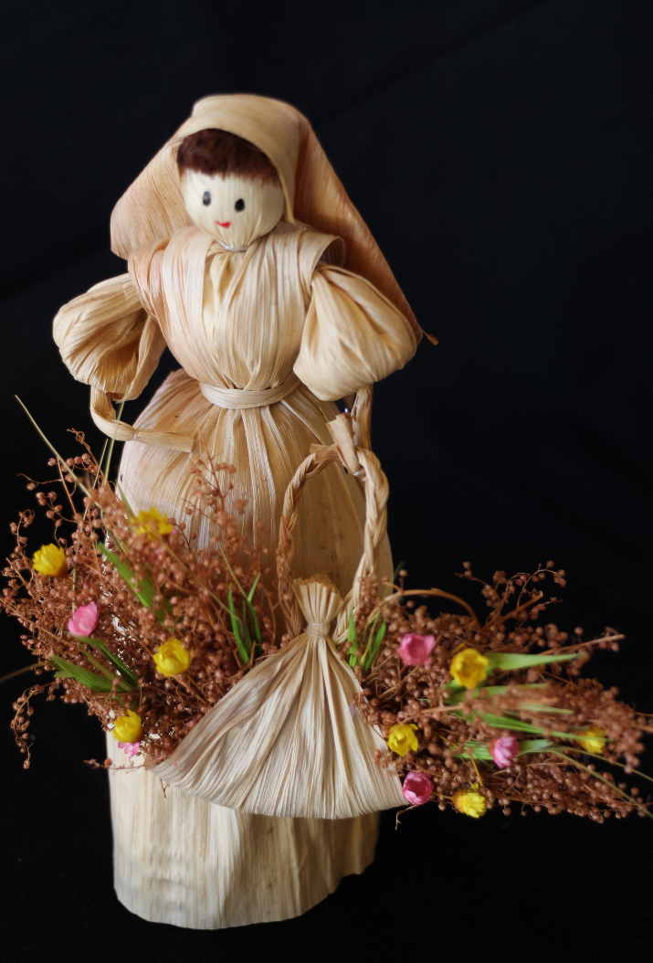 Corn doll carrying dried flowers in a basket.